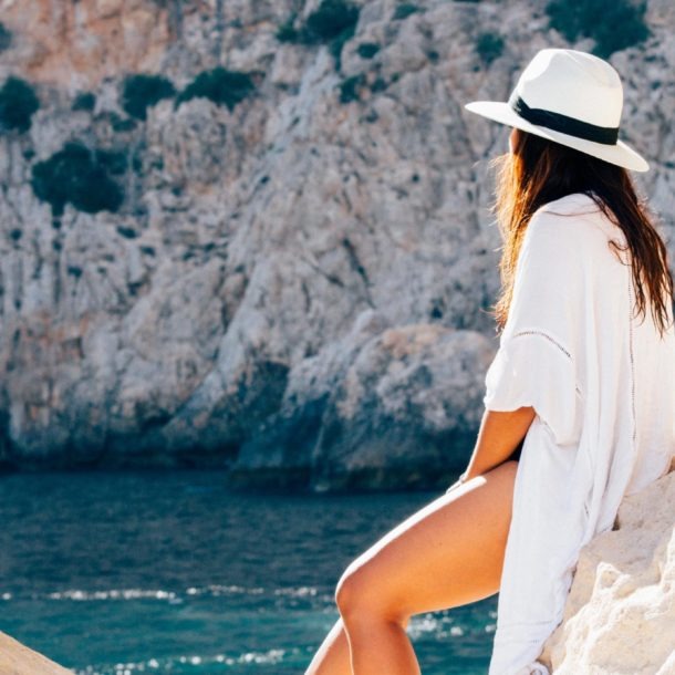 A woman in white sits with her back to the camera facing the blue ocean. She is surrounded by rocky terrain. The photo accompanies an article about travel.