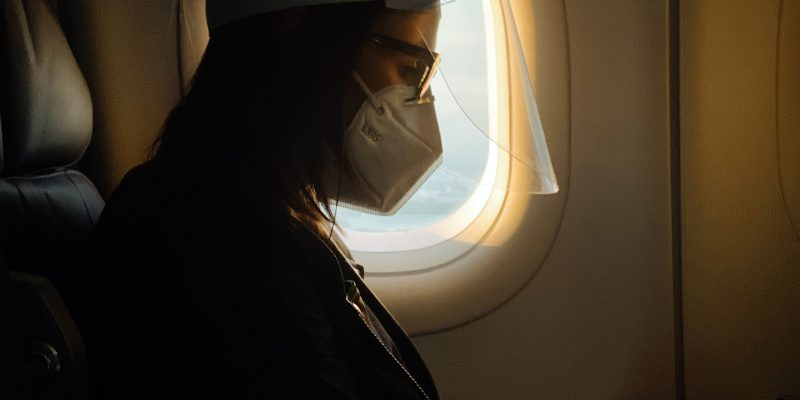 Woman on airplane adhering to CDC guidelines
