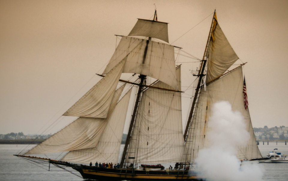 """A photo of an old sailing ship with all of its sails open. It accompanies an article about how to grow your business, examining the role of the East India Company as """"the first startup."""""""