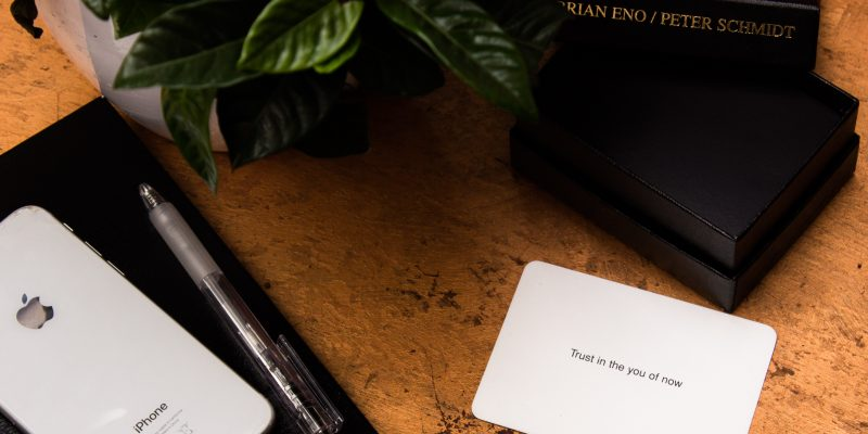 """A white card that says """"Trust in the you of now"""" sits on a brown table next to to black boxes, an iphone, and a plant. The card is from a pack designed to help people get inspiration, and possible grow your business."""
