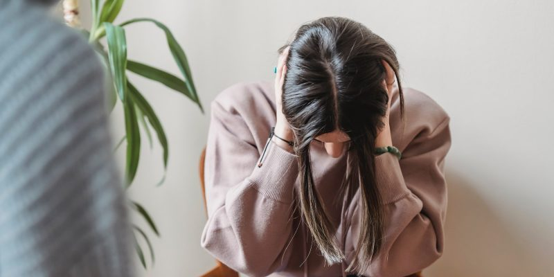 A photo of a woman leaning over while holding her head. It accompanies an article about fighting self-doubt.