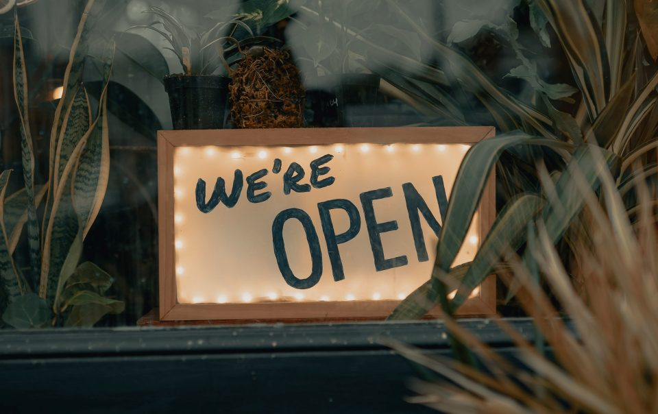 """A white sign with lights around the perimeter that says """"we're open"""" in black letters. The associated article seeks to help a reader in reopening their business"""