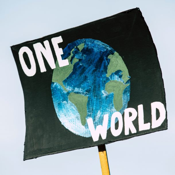 """A black sign with the earth and the words """"one world"""" on it at a climate rally. Protestors encourage corporations to make their businesses more sustainable."""