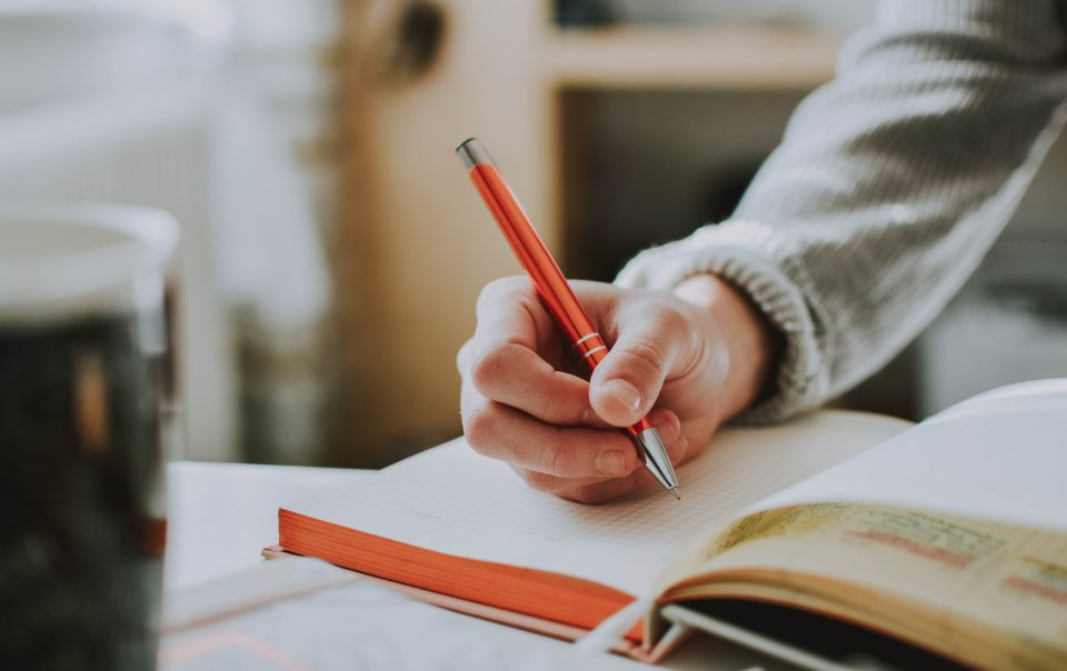 A hand writing in a book with an orange pen. The person is wearing a long sleeve gray shirt. The photo accompanies an article about getting an internship.
