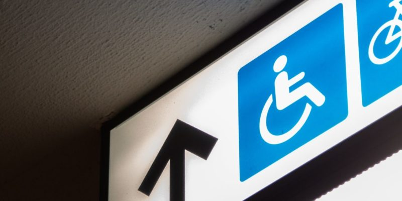 A fluorescent white sign on which there is a blue image of a person sitting in a wheelchair. Next to the image is a black arrow pointing forward. The image as a whole accompanies an article about increasing accessibility in one's business.