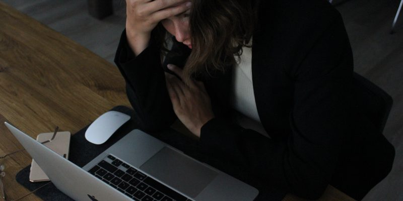 A woman sitting at a desk in front of a laptop with her head in her hands. It accompanies an article about hustle culture.