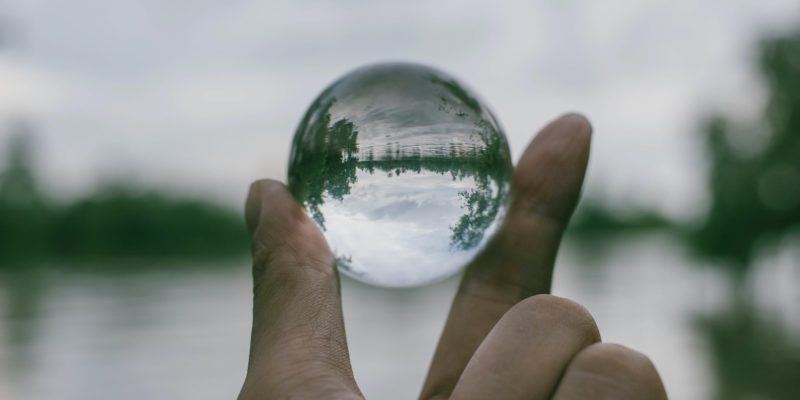 A hand holding a glass sphere, through which a lake can be seen. It accompanies an article about setting goals.