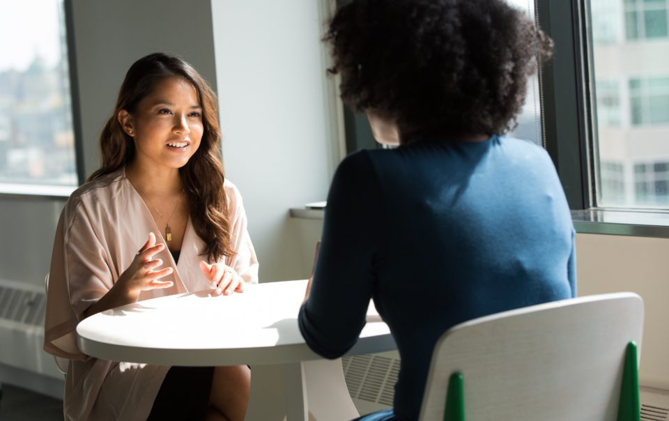 Two people sitting at a round table. One has long brown hair and is facing the viewer, and the other has an afro and is facing away from the viewer. The photo accompanies an article about business coaching.